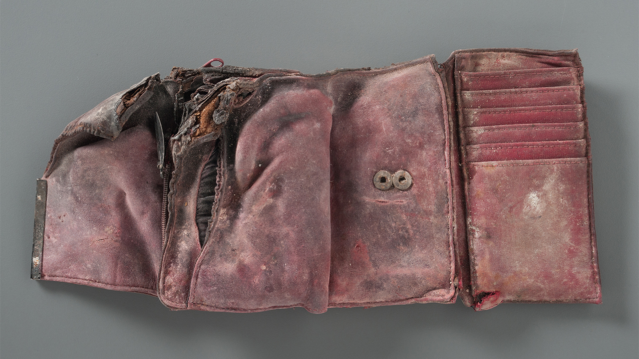 A damaged and stained red wallet is open on a gray surface. The wallet is empty. Its left corner is burned and ripped.