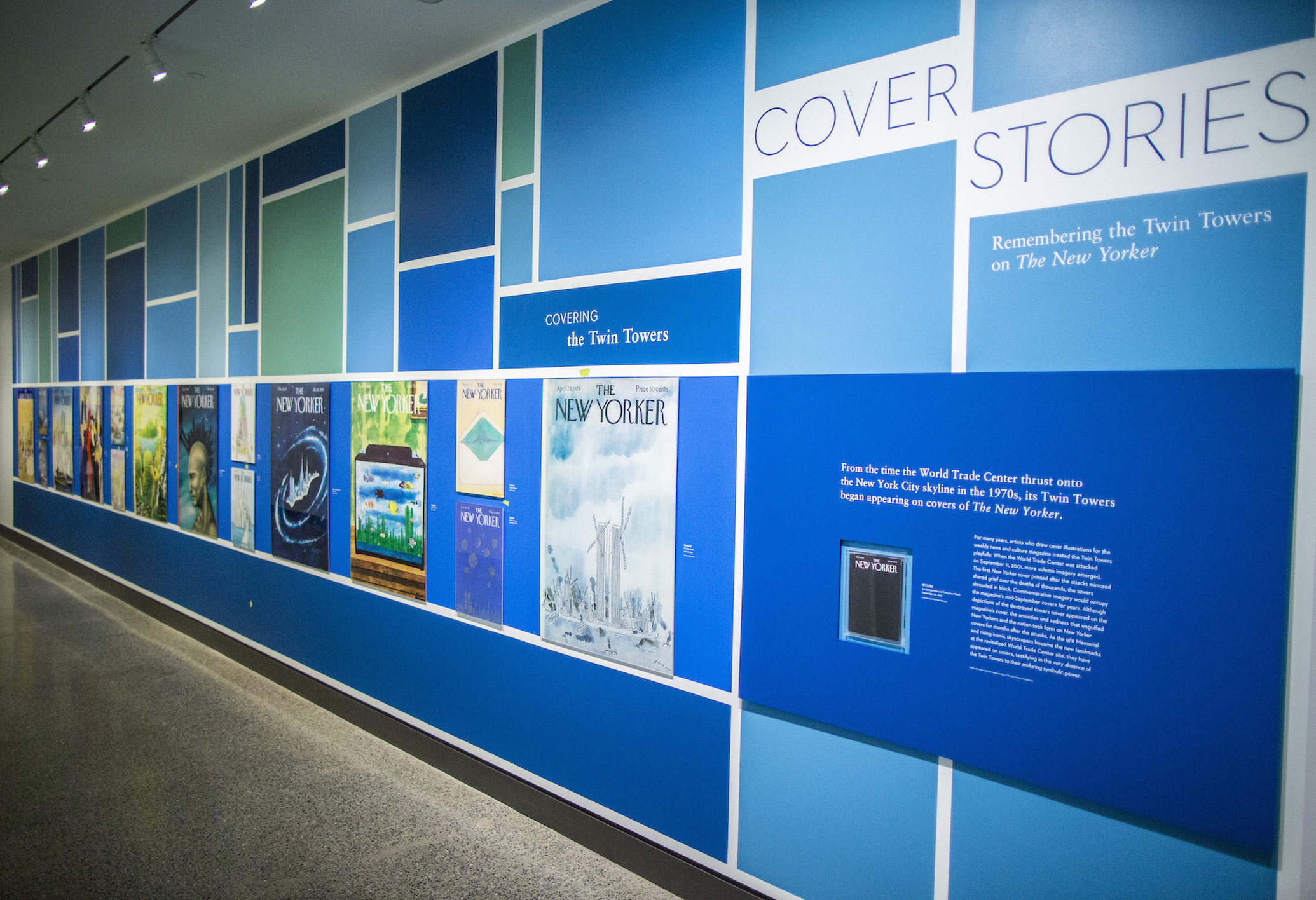 Images of Twin Towers–themed New Yorker covers are displayed on a wall as part of the exhibition Cover Stories.