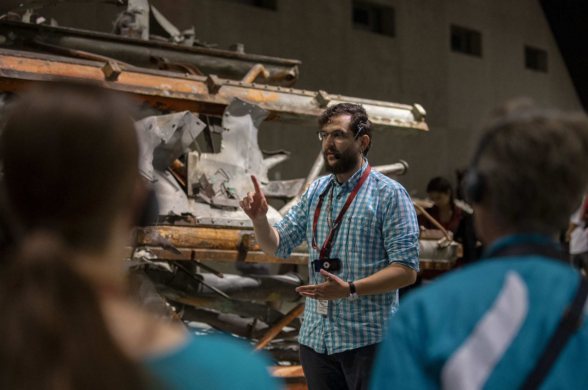 A male tour guide stands in front of the mangled antenna of Tower One as he talks to visitors on a guided tour in Memorial Hall.