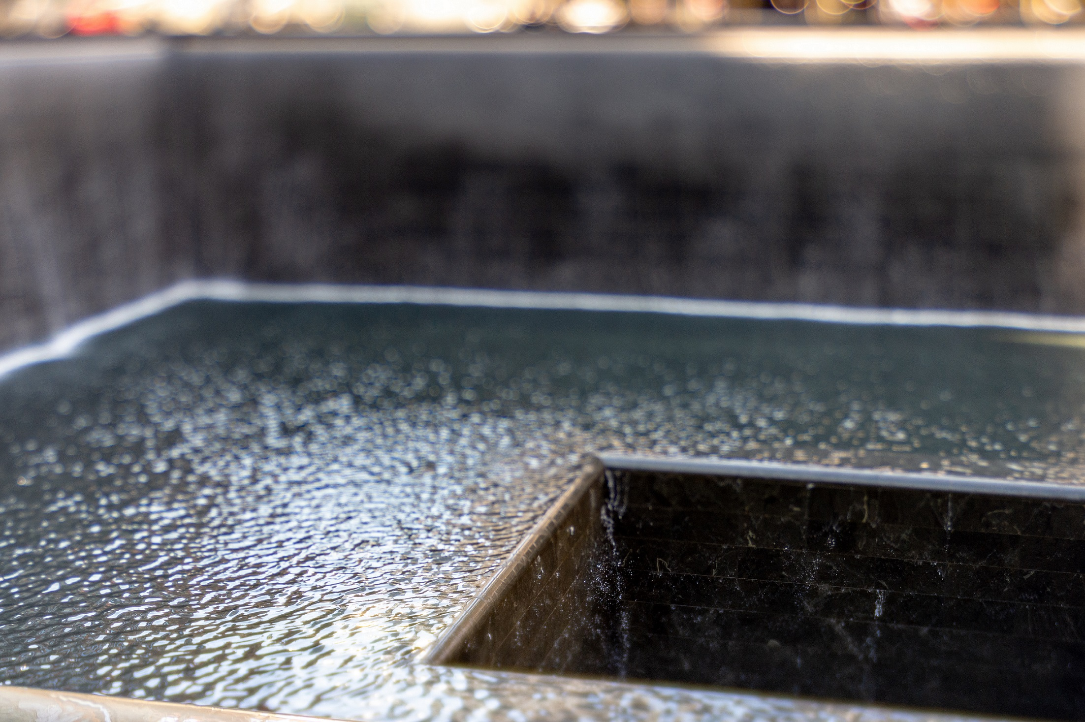 Water flows down two walls and disappears into a void at the center of a Memorial reflecting pool. Sunlight creates shadows on the pooled water.