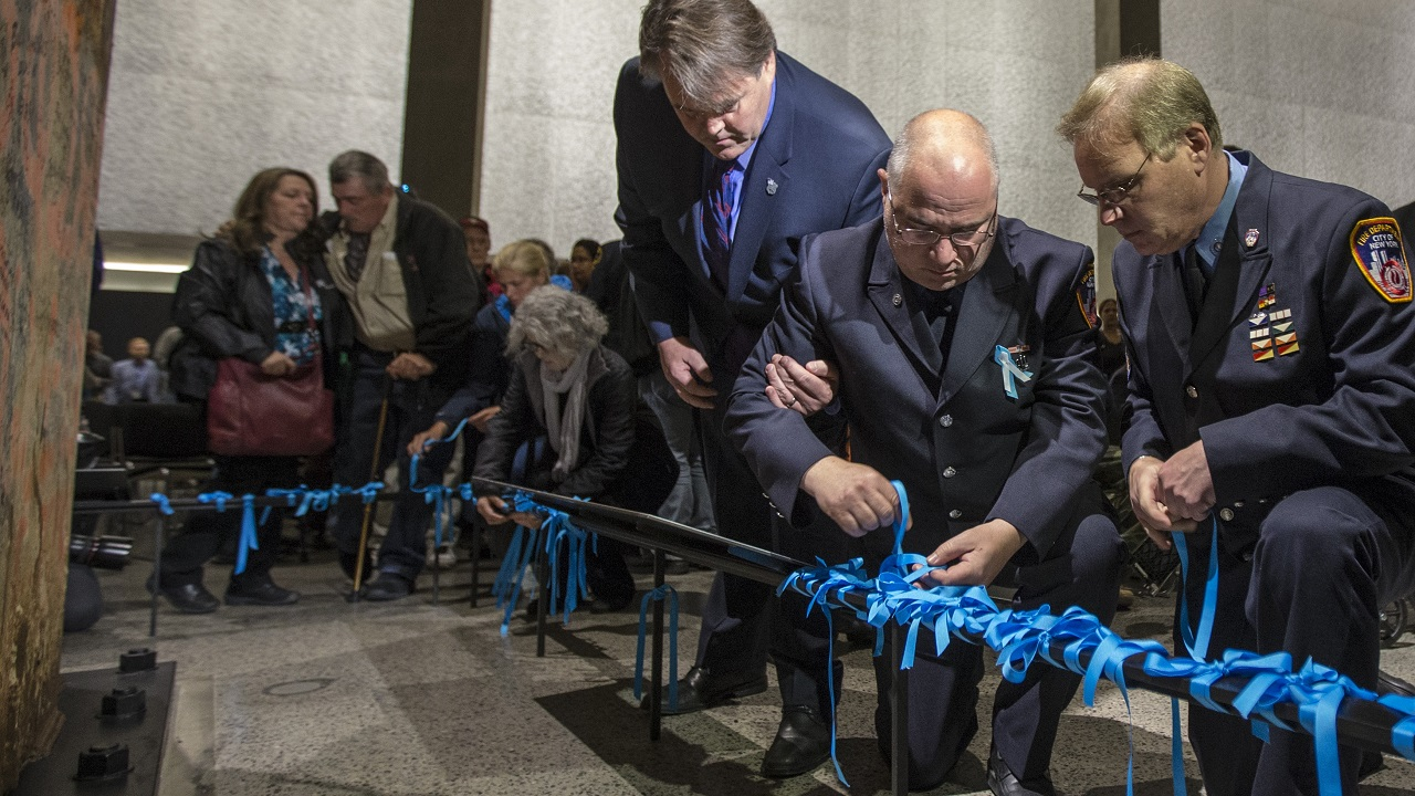 Several members of the FDNY and the family members place blue ribbons on a black railing at the foot of the Last Column.