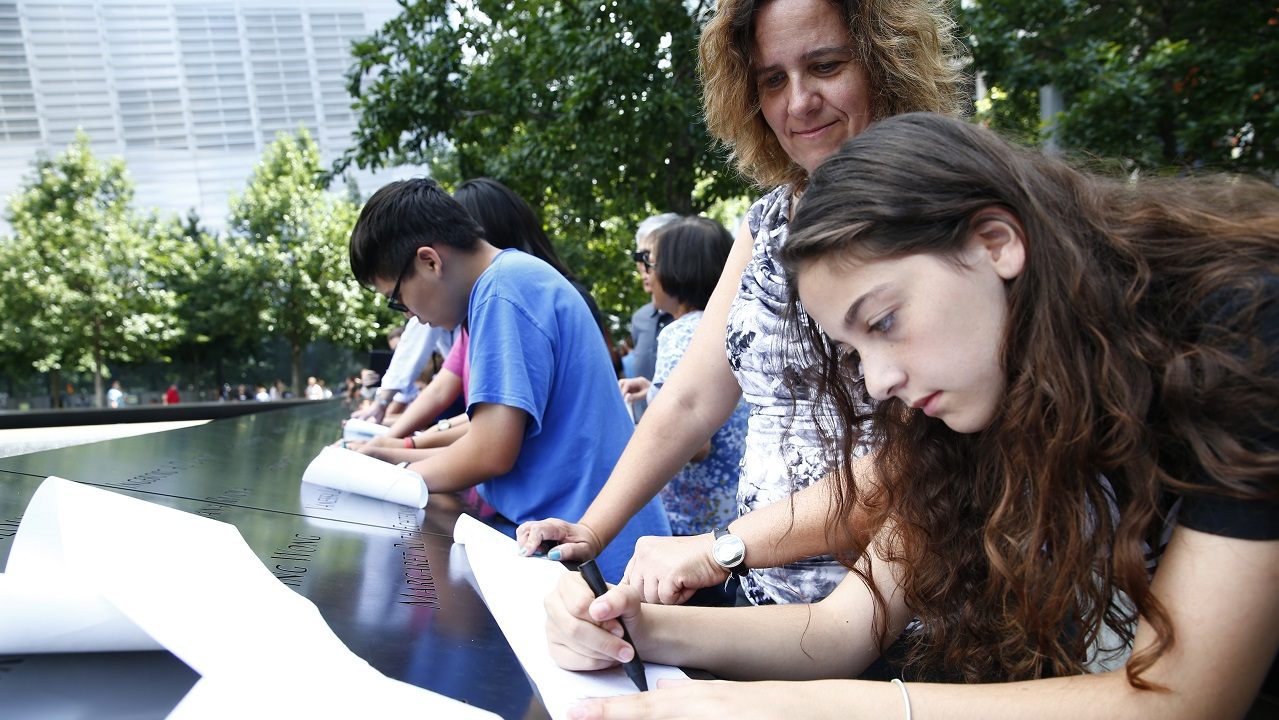 A teenage girl and a woman create a name impression at the Memorial by rubbing charcoal over a sheet of paper placed on an inscription. Other families beside them do the same along a bronze parapet inscribed with victims' names.