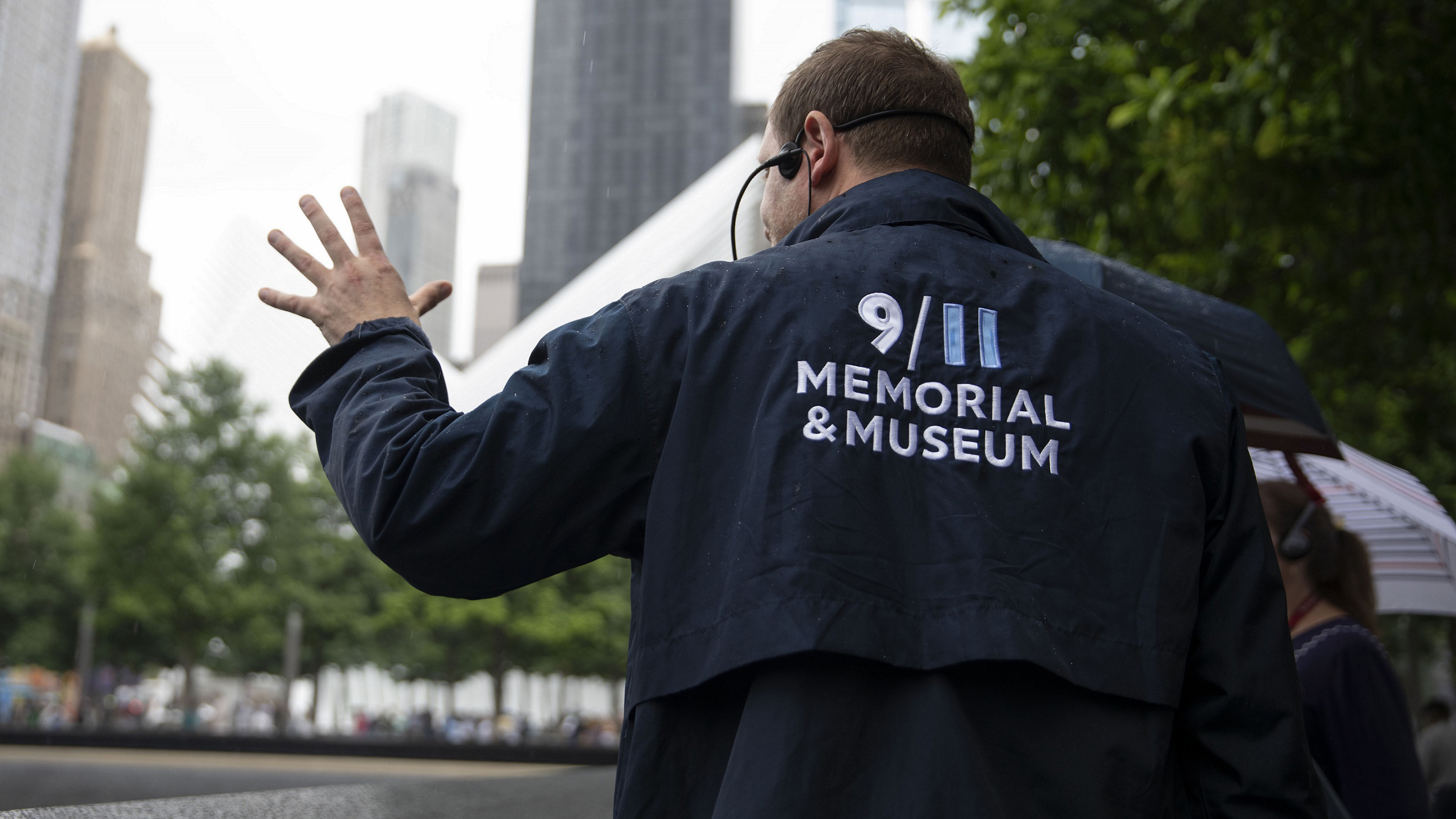A tour guide in a blue 9/11 Memorial & Museum jacket faces away and motions with his left hand as he shows visitors a reflecting pool at the Memorial.