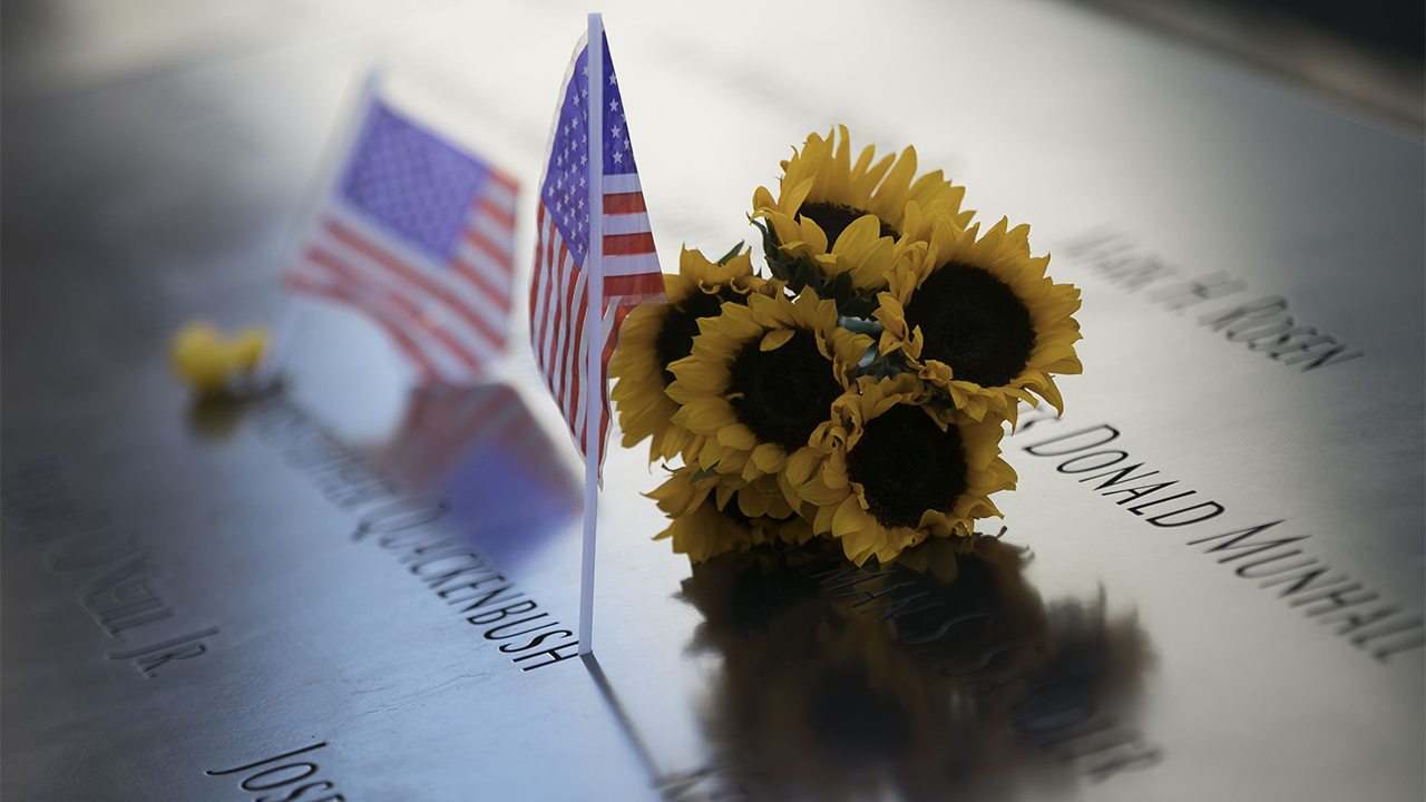 A bunch of sunflowers rest on the 9/11 Memorial, which is cast in a shimmery yellow and blue light. Two American flags rest alongside it.
