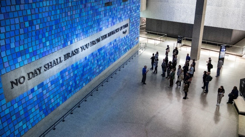 "An aerial view of a group visitors listening to a tour guide explaining about Virgil's quote forged out of World Trade Center steel. The quote, ""No day shall erase you from the memory of time,"" is surrounded by a sea of individual square tiles in different shades of blue."
