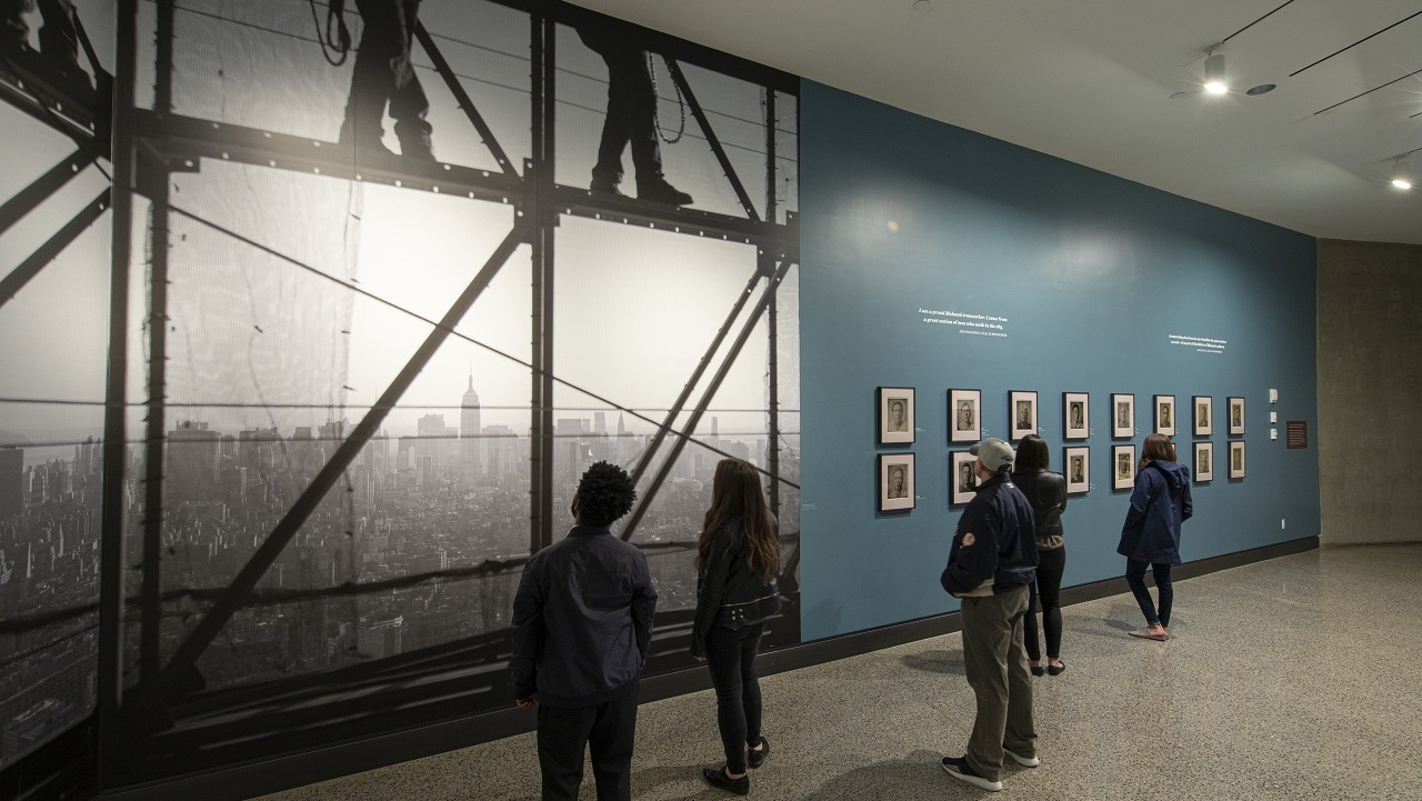 "Men and women looks at a large black-and-white photograph and 16 tintype photographs displayed on a blue wall, which is part of the special exhibition ""Skywalkers: A Portrait of the Mohawk Ironworker at the World Trade Center."""