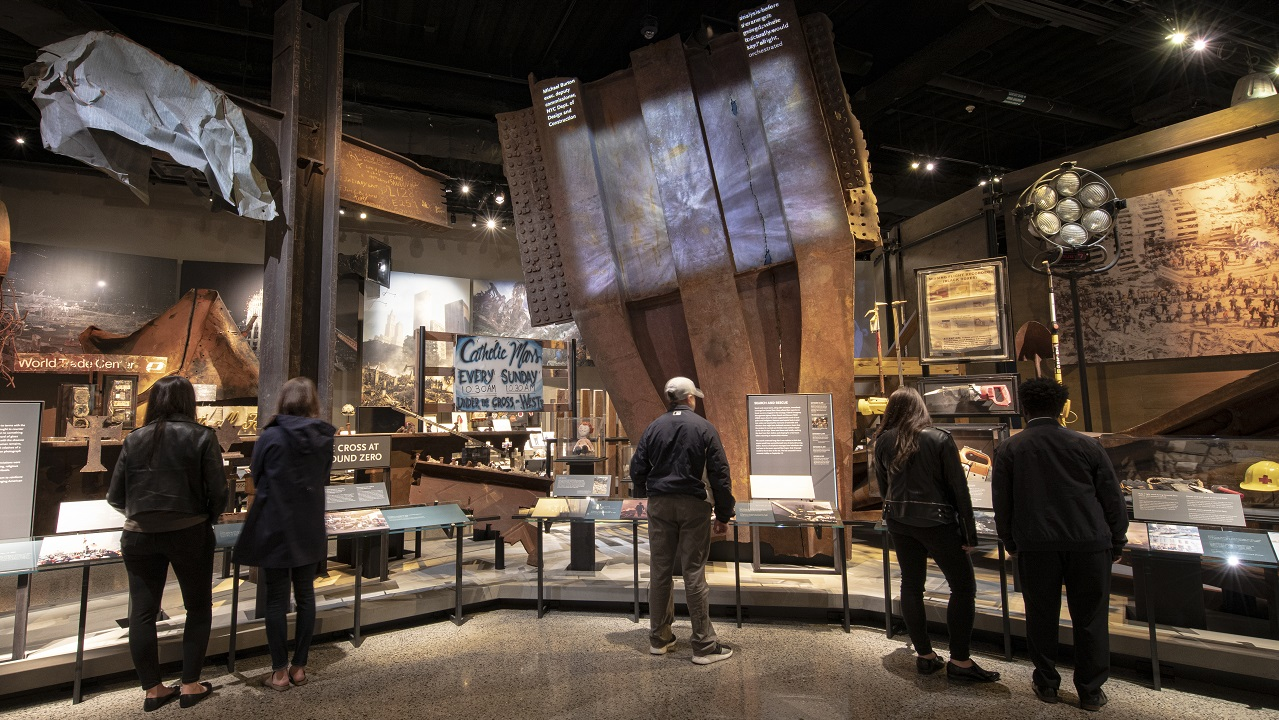 Visitors look at artifacts in the Museum's Historical Exhibition, including a large steel trident from a facade of the Twin Towers.