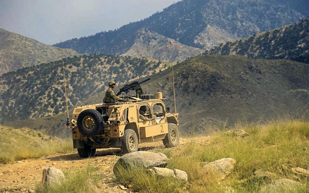 A soldier looks out on a mountainous terrain from an armored vehicle.