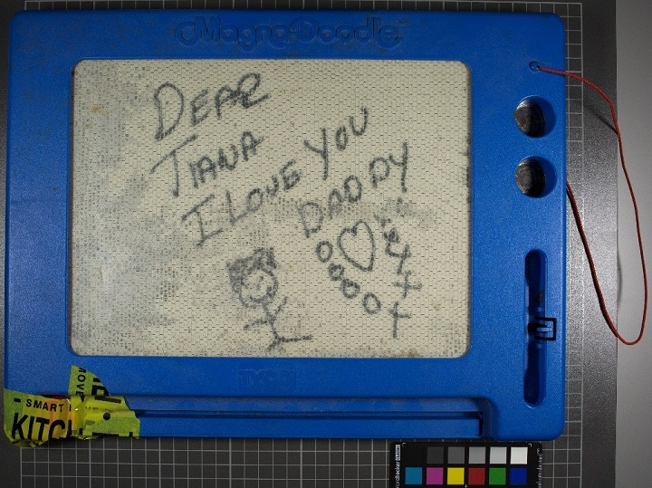 "A close-up photograph of a message inscribed on a Magna Doodle with a blue plastic frame. On the Magna Doodle screen is a smiling stick figure and a message: ""Dear Tiana / I Love You / Daddy."" Below the message is a drawing of a heart surrounded by x's and o's."