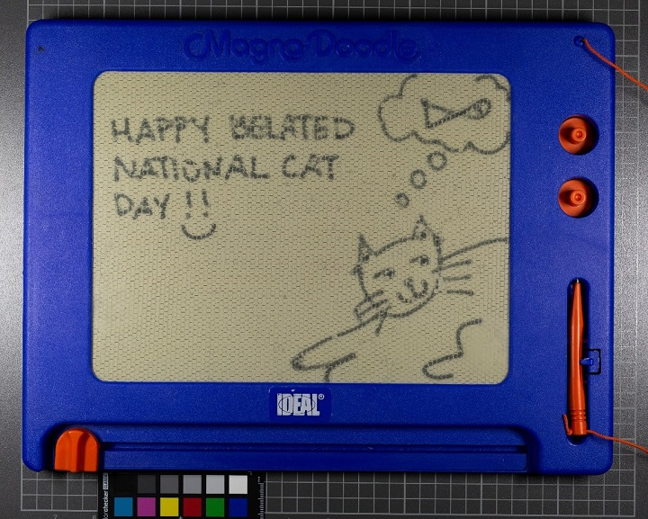 "A message and a drawing inscribed on a Magna Doodle that appears slightly newer than the Magna Doodle in the previous image. On this screen is a drawing of a smiling cat reclining, a thought bubble featuring a fish above its head, and a message: ""Happy Belated National Cat Day!!"" with a smiley face."