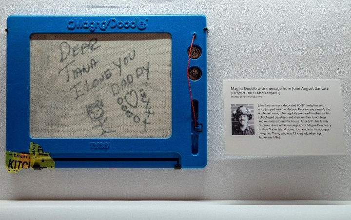 "A photograph of the Magna Doodle affixed to an exhibition item display case in the ""In Memoriam"" gallery."