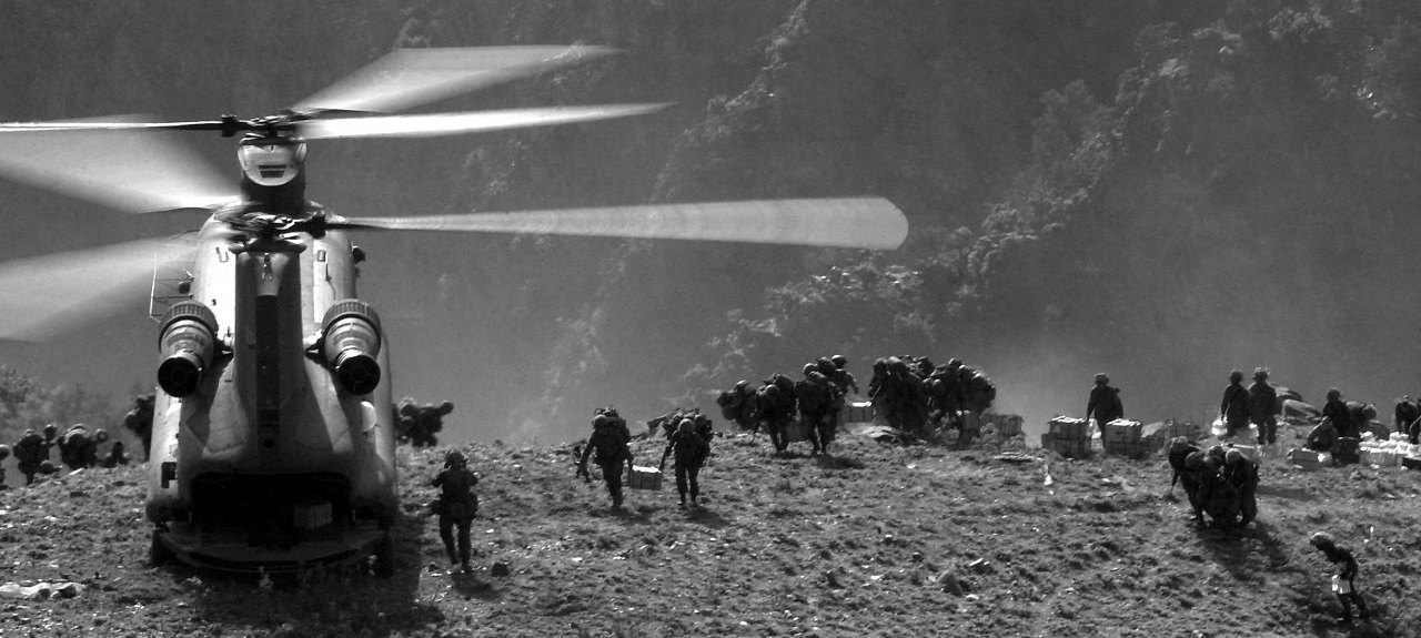 Back view of soldiers carrying supplies from a helicopter on mountaintops.
