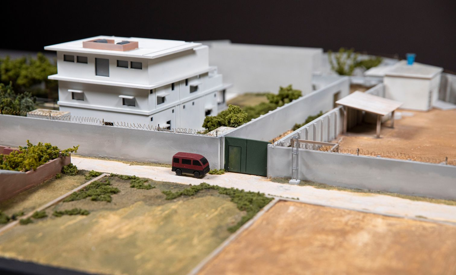 Aerial view of model of a walled white compound surrounded by predominantly brown landscape.