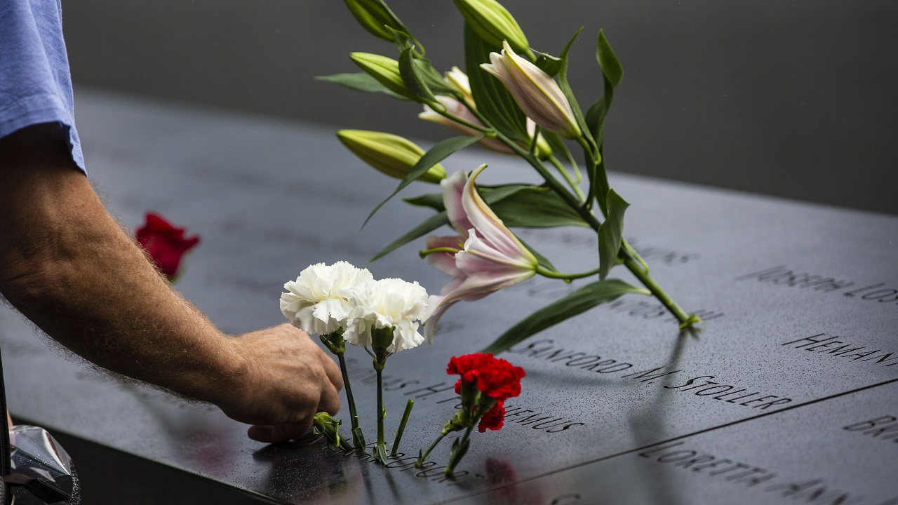 A family member places a white carnation in a name on a memorial panel.  His arm is extending into the frame from the left side as he add a carnation to row flowers placed inside the name.