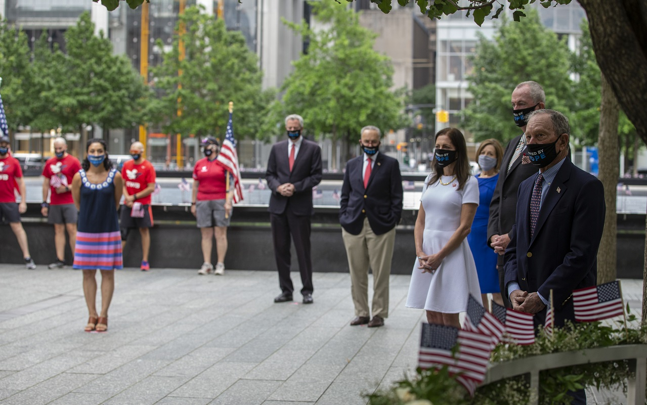 Dignitaries stand socially distanced and wearing face masks during a small ceremony on the 9/11 Memorial plaza.