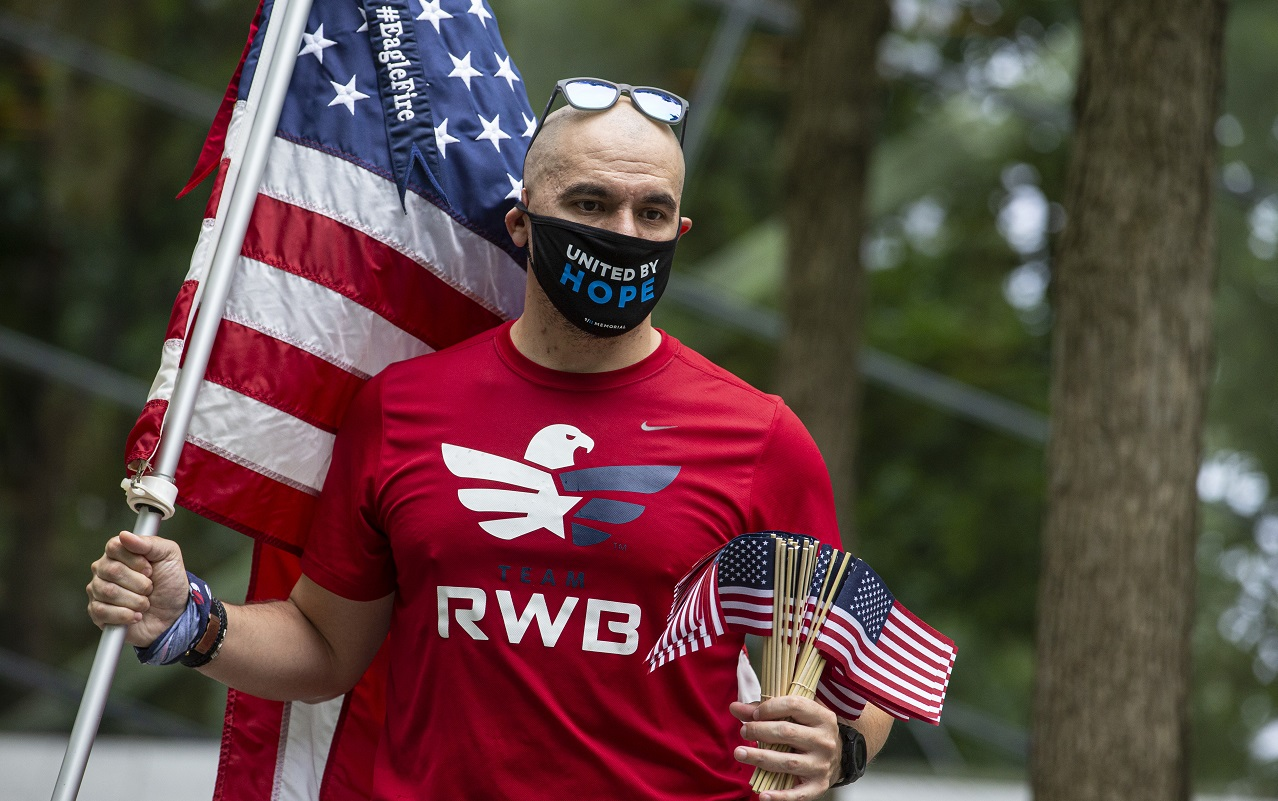 "A man waving an American flag and wearing a T-shirt that reads ""Team Red White & Blue"" wears a face mask and is about to hand out small American flags."