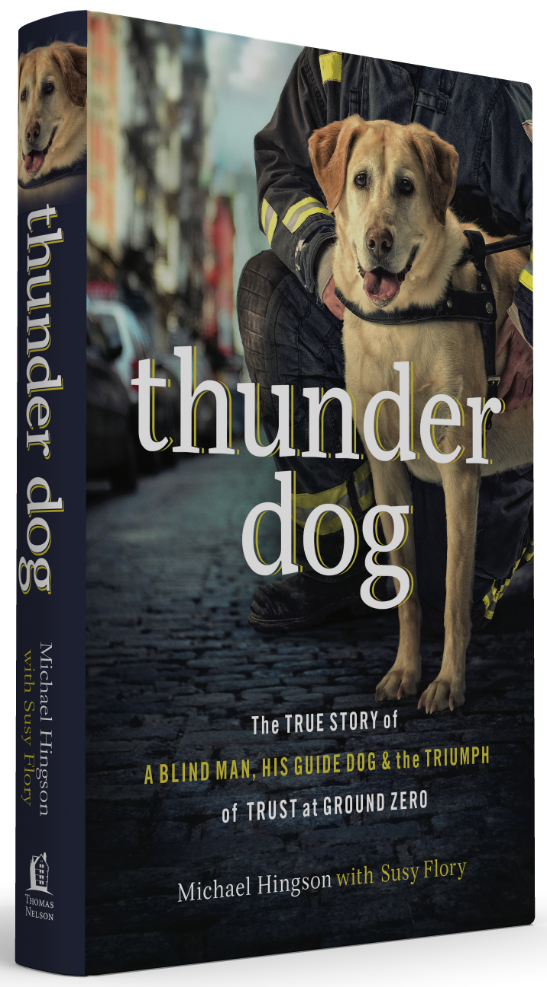 "A book cover of ""Thunder Dog,"" featuring a yellow lab with a black collar standing on a city street. A firefighter kneels behind the dog, but his face is not visible."