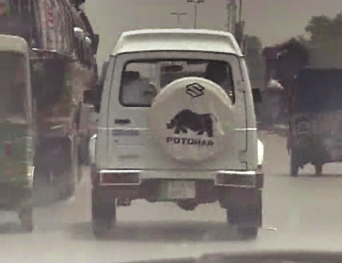 Still from video of the back of a white van with animal logo on the back on the road.
