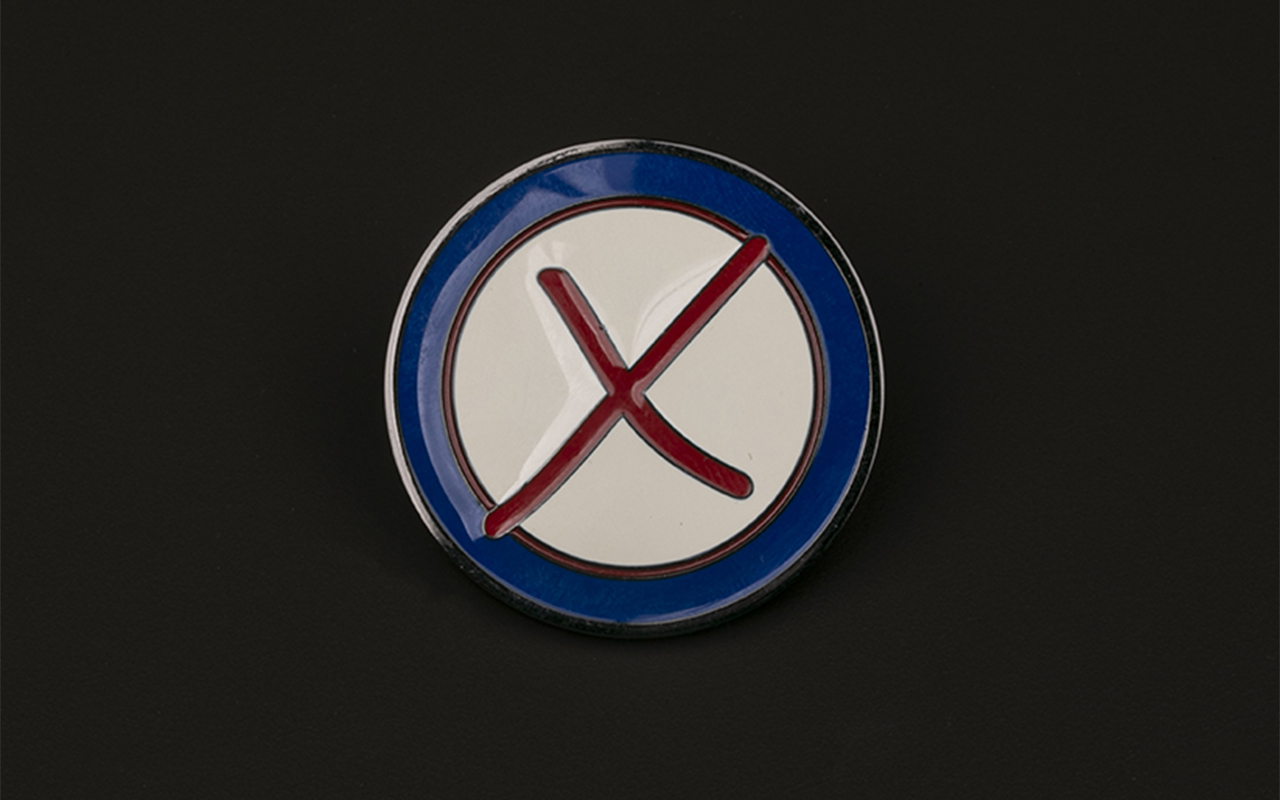 A challenge coin with a raised red X in the center of an ivory circle and a navy blue border is suspended against a black background.