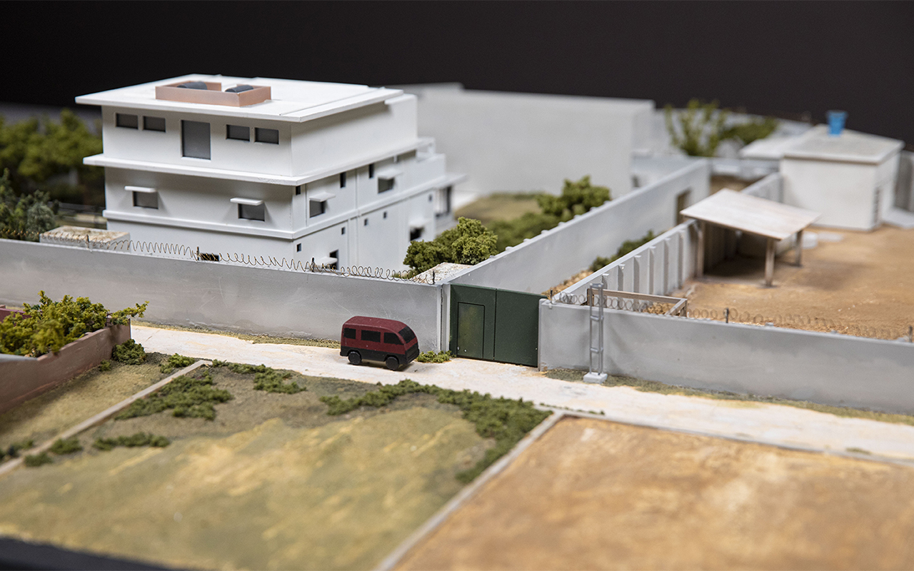 A model of the white and gray compound that housed bin Laden rests on a bed of dry-looking grass. A red courier van is parked out front.