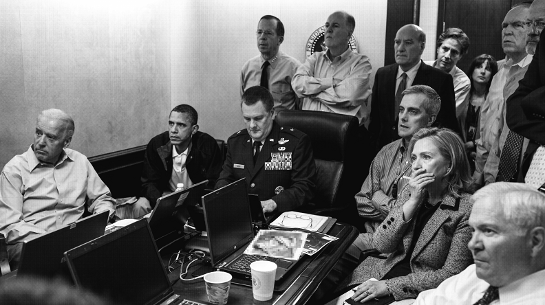 President Obama, Vice President Biden, Secretary of State Hillary Clinton, and other people sitting and standing around a conference table watching offscreen.