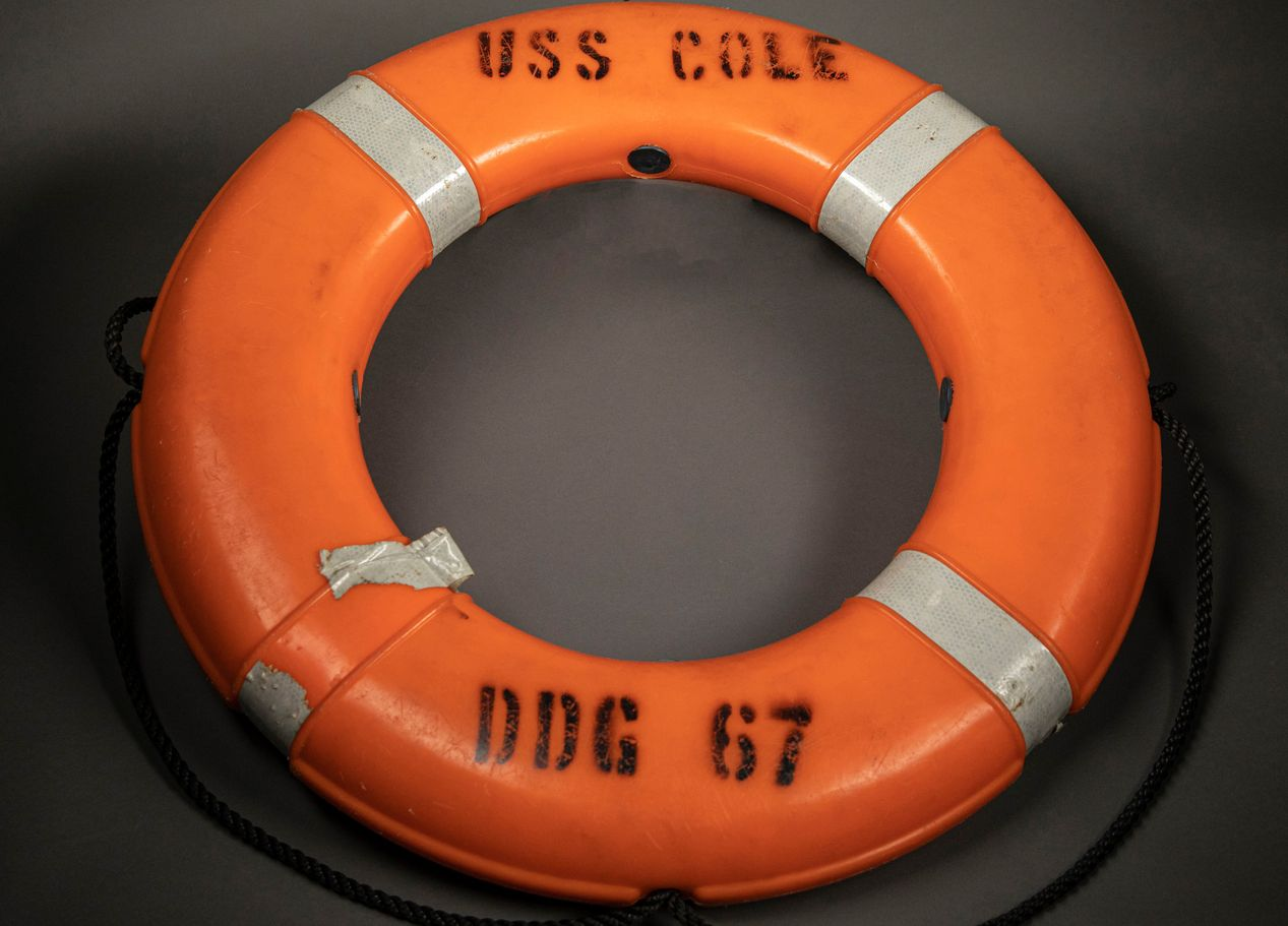 "Orange life ring with the words ""USS COLE"" and ""DDG 67"" stamped on it."