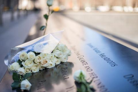 A bouquet of white roses has been left at a name on the 9/11 Memorial. A single yellow rose is seen placed at a name in the background.