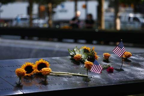 Yellow roses, sunflowers and two, small American flags are seen on a bronze parapet at the 9/11 Memorial.