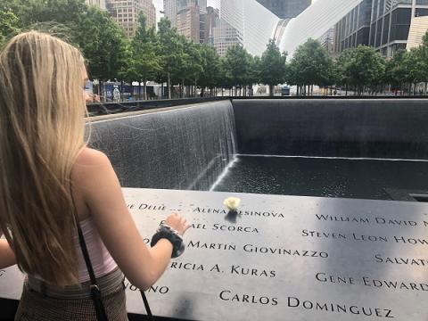 Caleigh Leiken's back is turned to the camera as she places a white rose at the name of Alena Sesinova at the 9/11 Memorial. Water cascades down the sides of a reflecting pool in the background.