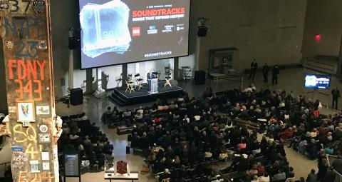 "More than 500 people are seated as they attend a special Tribeca Film Festival screening of CNN's ""Soundtracks: Songs That Defined History."" A man is onstage in front of a large screen in Foundation Hall, and the Last Column can be seen in the foreground."