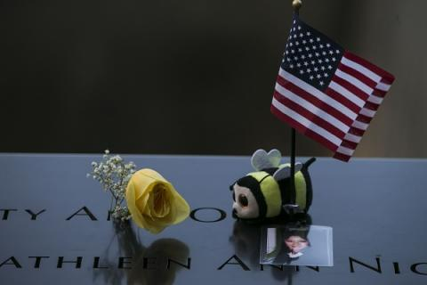 A stuffed bumble bee, a yellow rose, a small American flag, and a photo of a victim of the 9/11 attacks have been placed at a name on the Memorial.