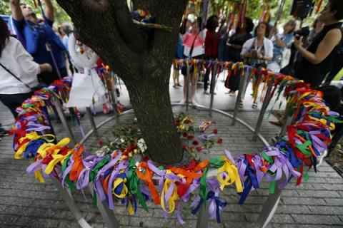 Dozens of ribbons in every cover of the rainbow are seen tied to a railing surrounding the Survivor Tree on the second anniversary of the Pulse nightclub shooting. Some in the background take photos of the tree as others tie ribbons on the branches of the tree.