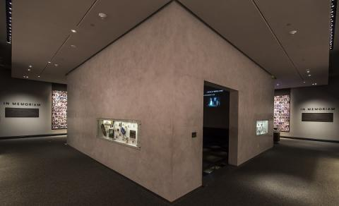 An interior look at the In Memoriam exhibition. Personal artifacts that belonged to victims are displayed on the walls of an inner chamber in which their profiles are projected. Some of the 2,983 portrait photographs of victims are on walls to the left and right of the chamber.