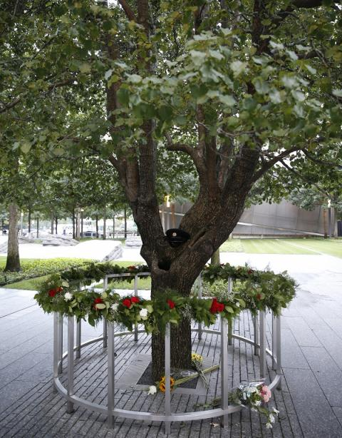 Flowers and other tributes have been left at the Survivor Tree on Memorial plaza. A first responder's formal hat has been placed on the tree's trunk.