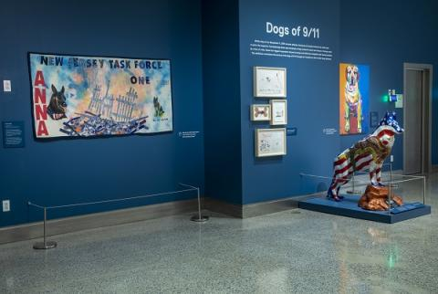 "The exhibition ""Dogs of 9/11"" is seen at the Museum. It includes artwork of dogs and a statue of a dog in the colors of the American flag."