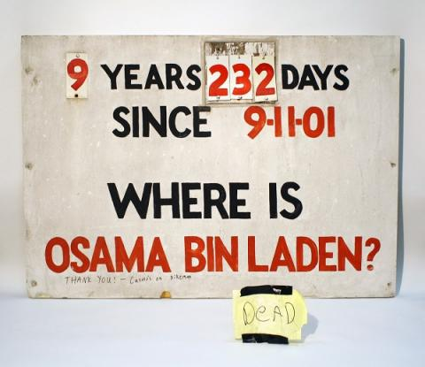 "A sign that tracked the days Osama bin Laden was at large is displayed on a white surface. The sign reads: ""9 years, 232 days since 9/11/01. Where is Osama bin Laden?"" A yellow piece of paper beside the sign reads ""Dead."""