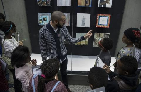 Middle school students from Macademy School of Science and Technology take part in a guided student program. An education specialist points out objects displayed in a glass case as the students look on.
