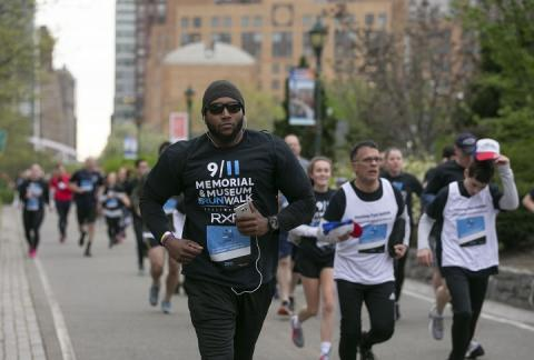 A man with a black hat, sunglasses, and black running outfit leads a pack of runners on an overcast day.