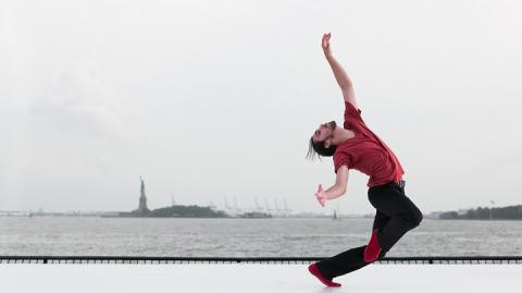 A ballerina dancer in red shirt and black leggings performs on a white platform. The Statue of Liberty is visible in the distance.