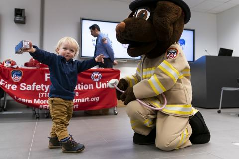 A blond toddler stretches his arms to greet a man in a dog suit.