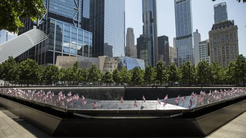 A view of American flags inserted into the names parapet. In the background are the skyscrapers of the World Trade Center.