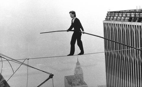 In this black-and-white historical photo, Philippe Petit holds a long pole as he does a hire-wire walk between the Twin Towers. The buildings of lower Manhattan can be seen below him.