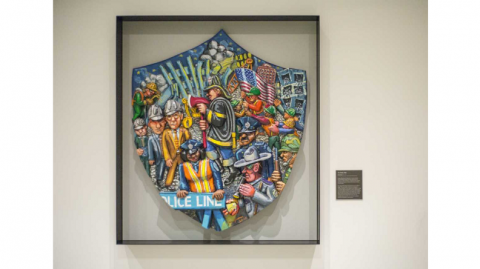 Enamel on epoxy sculpture by Red Grooms titled The Shield. The large piece is designed in the shape of a shield with a three dimensional collage of characters rendered with cartoon-like appearances and painted in bold colors.