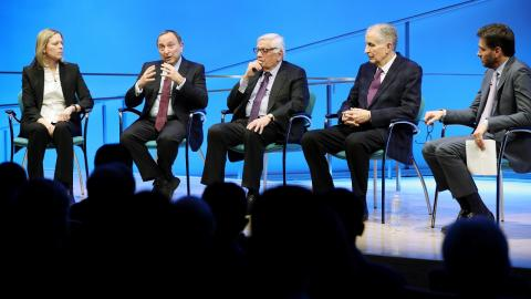 A woman and four men sit onstage while taking part in a public program about sports after 9/11 at the Museum Auditorium. To the left is WNBA Founding President and Big East Conference Commissioner Val Ackerman. To the right of her is NHL Commissioner Gary Bettman, who is speaking while gesturing with both hands. To the right of him is NBA Commissioner Emeritus David J. Stern. To the right of him is former NFL Commissioner Paul Tagliabue. At the far right is Mike Greenberg, longtime SportsCenter anchor and c