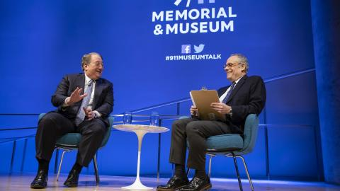 Real estate owner and builder Howard Milstein gestures with his left hand as he sits on the Museum Auditorium stage with moderator Clifford Chanin, executive vice president and deputy director for Museum Programs. Milstein and Chanin are both smiling as they sit on the stage, which is bathed in blue and white light. A white table with two glasses of water sits between the two of them.
