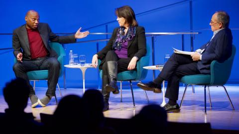 Three public program participants sit on a blue-lit auditorium stage. To the far left, a man in a gray blazer, red sweater, and jeans gestures with both arms, his face holds an expression of incredulity. A woman in the center and the moderator look on. The heads of the audience members appear in the foreground in silhouette.