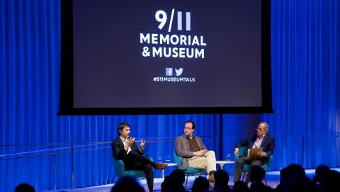 "Three men in suits sit on a blue-lit auditorium stage. Behind them ""9/11 Memorial & Museum #museumtalk"" is projected on a screen behind them."