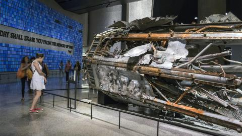 A woman in a white dress looks at a damaged portion of the North Tower's massive broadcast antenna displayed on its side at the Museum.