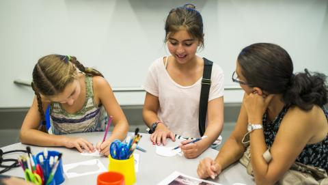 Two girls are engaged in an art activity in a classroom setting while a woman sharing their table looks on attentively.