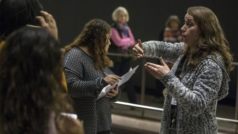 A woman holds up her hands as she speaks to a group of students at the Museum. To her right is one student who is holding a pencil and clipboard in her hands while looking down at something out of view.